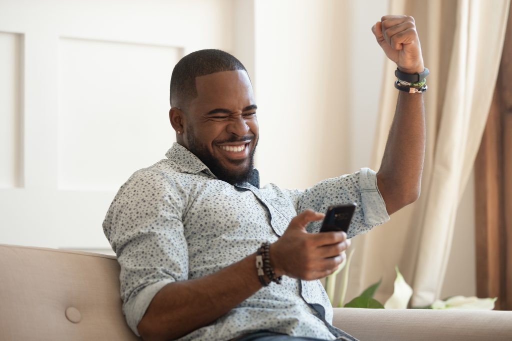 Overjoyed black man holding smartphone feeling euphoric with mobile win