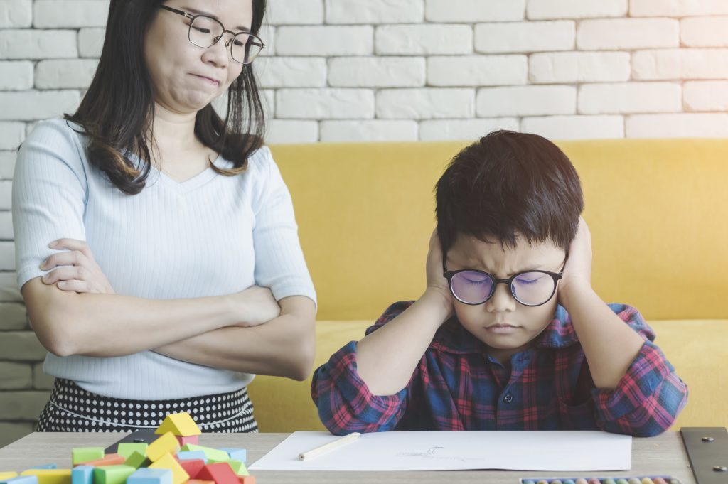 Mother helping her is son with difficult homework task scold him for being dumb on table in the room.